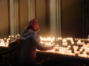 Kinder entzünden im Salzburger Dom eine Kerze für ein verstorbenes Familienmitglied